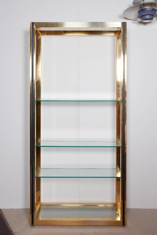 A linear Mid-Century Modern étagère produced circa 1970s and designed in the style of Milo Baughman, in brass and faux leather detailing with glass shelves. Very good vintage condition with age appropriate wear; glass requires