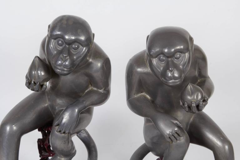 A pair of Chinese export monkey sculptures in pewter, produced circa late 19th century, obtained from the estate of Consuelo Vanderbilt, each depicted holding a peach of immortality, on carved wood stands. Very good antique condition, one monkey