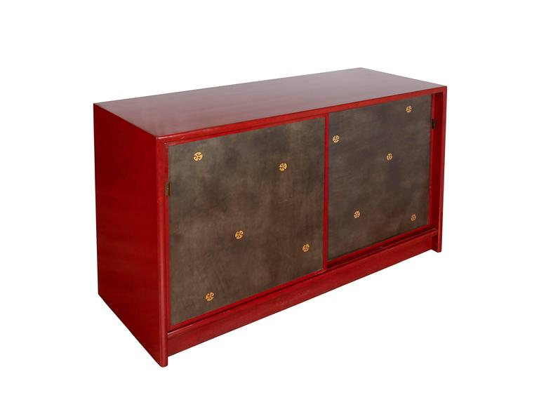 A pair of Mid-Century Modern Asian inspired cabinets or sideboards, in the style of designer Tommi Parzinger, each with red lacquer finish, including sliding doors decorated with gilt medallions, the completely gilded interiors with shelving space.