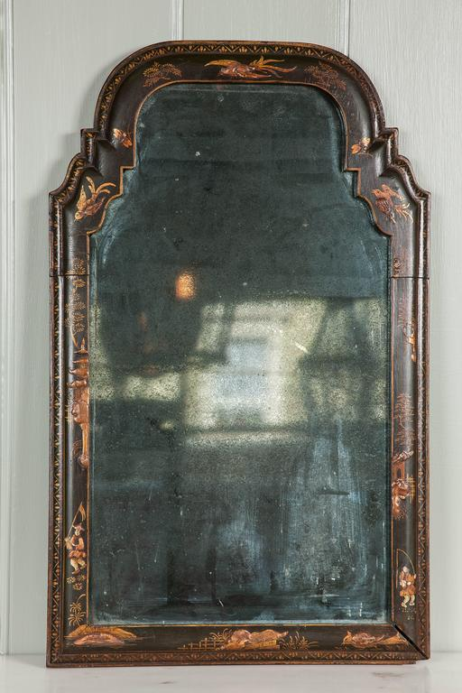 A rare Queen Anne wall mirror of small size with beautifully patinated arched mercury plate within a black and gilt lacquered moulded frame,  English, circa 1710.