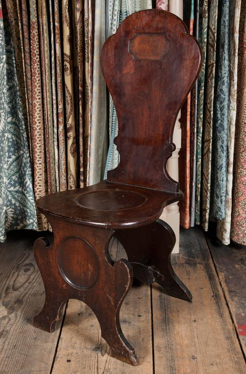 A pair of George II mahogany hall chairs with shaped backs and seat on scroll feet.