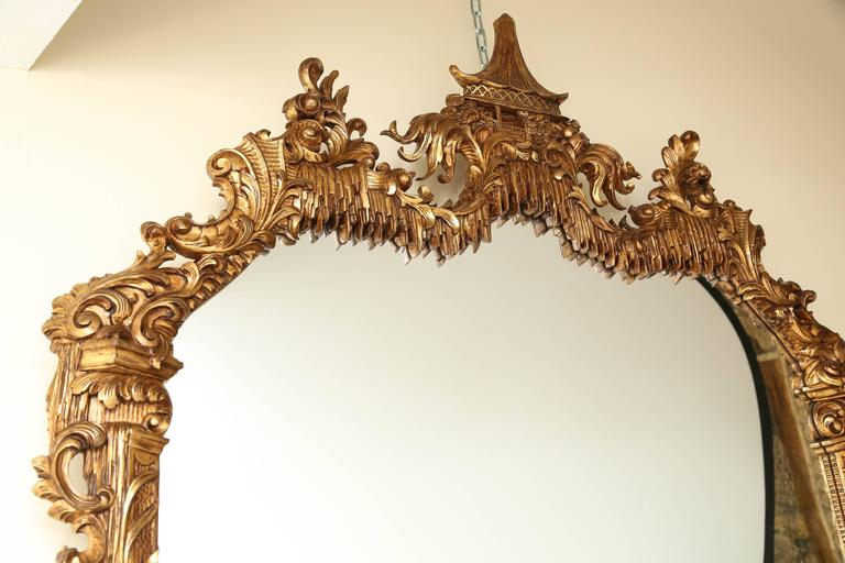 Magnificent giltwood mirror. In the Chinese Chippendale Style. Adorned with acanthus leaves, elegant scrolled carvings. Crowned with a Pagoda style pavillion surmounted in a 'floating' garden setting with a lambrequin apron. Bottom Apron featuring a