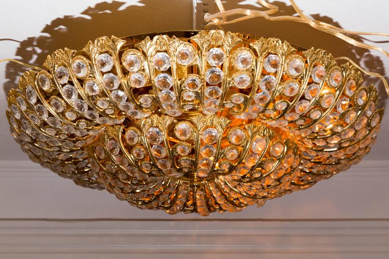 Dome form gilt metal flush mount fixture with inset crystal elements.