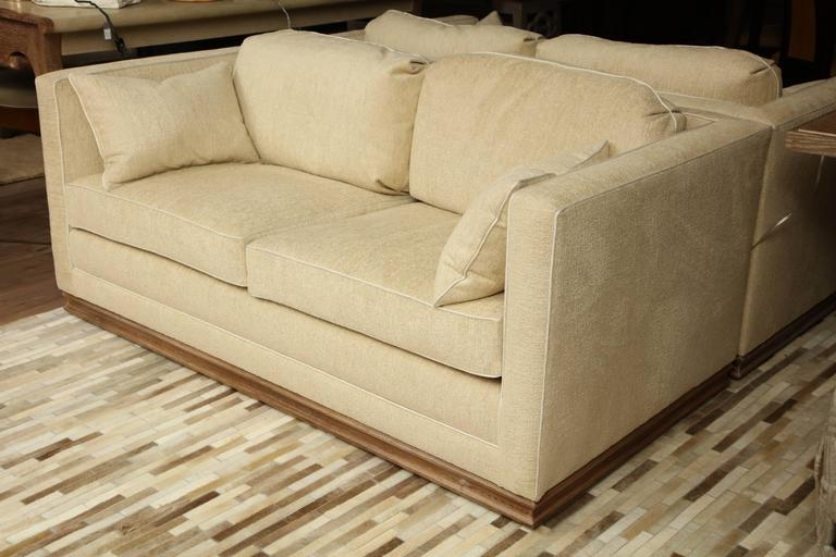 Pair of restored settees upholstered in cream chenille with a French twill welt on cerused oak platform bases, circa 1950.
