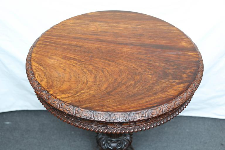 Rare and stunning rosewood table, original patination and color. Elaborate carving with vine and foliage apron. An exquisite example.