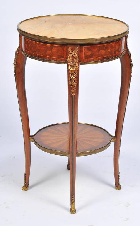 A 19th century French kingwood occasional table, having a sienna marble top, ormolu mounts, a single frieze drawer, raised on four cabriole legs, united by a circular under-tier which has radiating inlaid decoration.