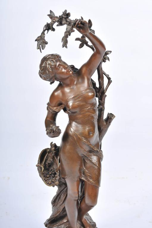 A very good quality, beautifully patinated bronze statue of a semi clad young girl picking cherries. Signed: Math. Moreau.