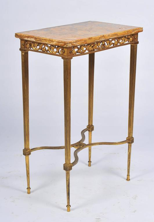A good quality late 19th century gilded ormolu, Sienna marble topped Louis XVI style side table Having pierced scrolling foliate decoration to the frieze and raised on square tapering legs, united by an cross stretcher.