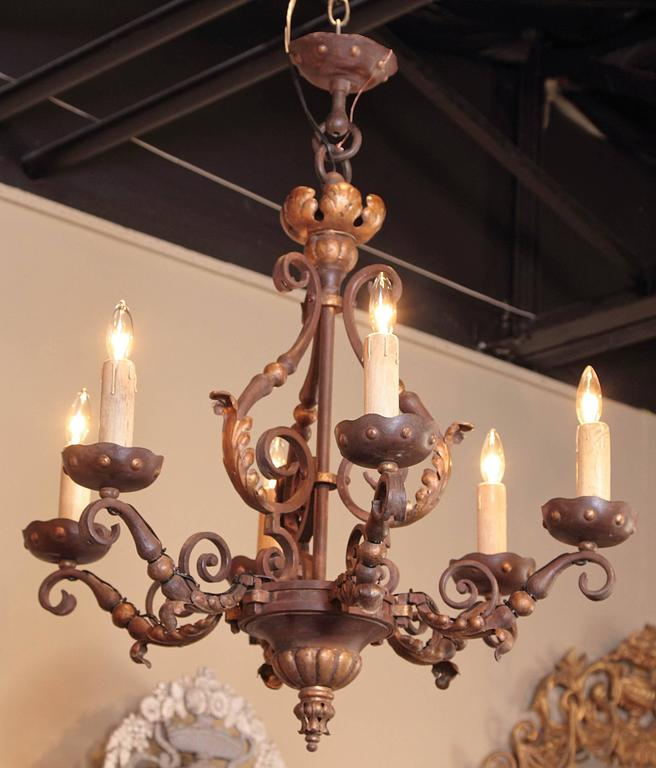 This elegant, antique, iron chandelier was created in France, circa 1890. The scrolling, Baroque fixture features its original verdigris paint with gilt accents. Around the chandelier are six lights, which have been rewired and have their original