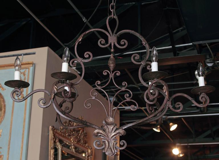 This elegant, scrolling, oblong chandelier would make a lovely addition to a home of any style. Crafted from iron, the light fixture was made in France, circa 1900. The chandelier features six scrolled arms newly wired, and curling center finial at