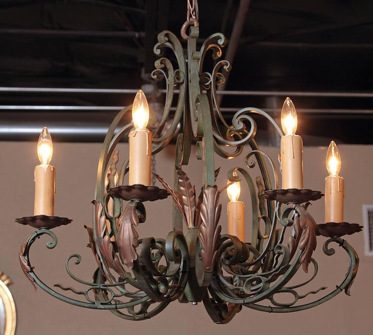This turn of the century iron chandelier would make a beautiful decorative addition to a bedroom, breakfast room or living room. Crafted in France, circa 1920, the rustic light fixture has a scrolling base and six scrolled arms with their original