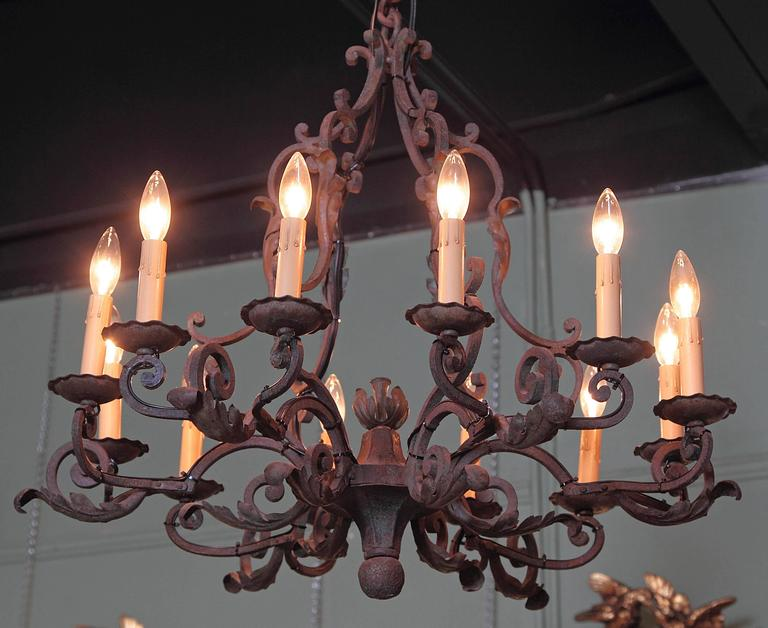This elegant, antique chandelier was created in France, circa 1900. The round, iron light fixture features ten scrolled arms with light, decorative, high relief leaves, and a center floral finial at the base. The fixture has new wiring for easy use