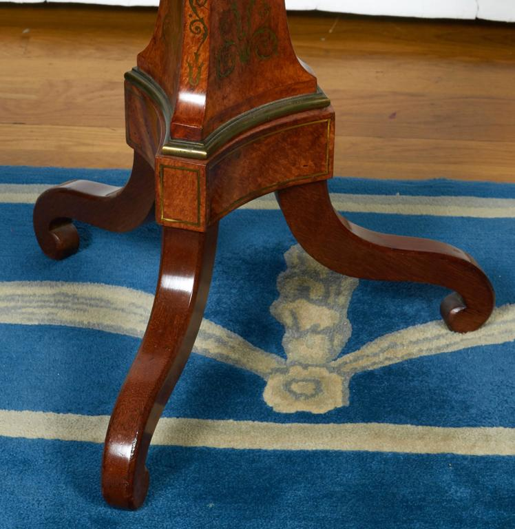 A burled walnut tea table with dish top, Edwardian style with brass inlaid trefoil motif to the top and the base, terminating in tripod scroll feet.