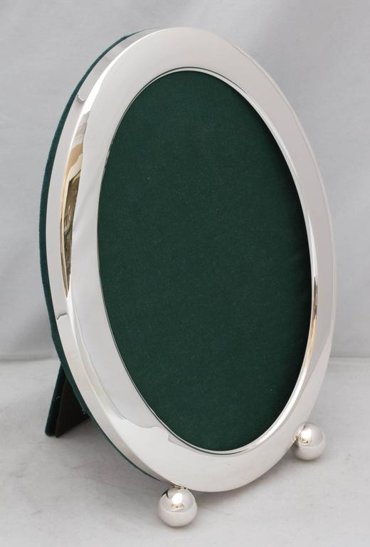 Large, Edwardian, sterling silver, oval picture frame on ball feet, The Webster Corp., No. Attleboro, Mass., circa 1910. Measures: 11 inches high x 5 inches deep (when easel is in open position) x 8 inches wide at widest point. Border is 1 inch