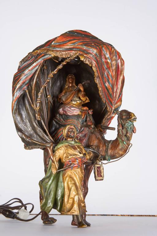 """A very fine antique Austrian cold painted orientalist bronze lamp of a princess playing a musical instrument sitting on a camel being led by an orientalist soldier, by Bergman. Measures: Height 14"""" Width 9""""."""