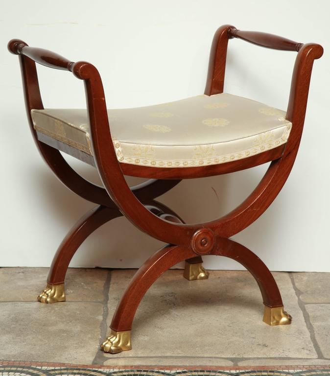 A pair of Directoire Curule mahogany benches with gilt bronze animal paw-form feet.