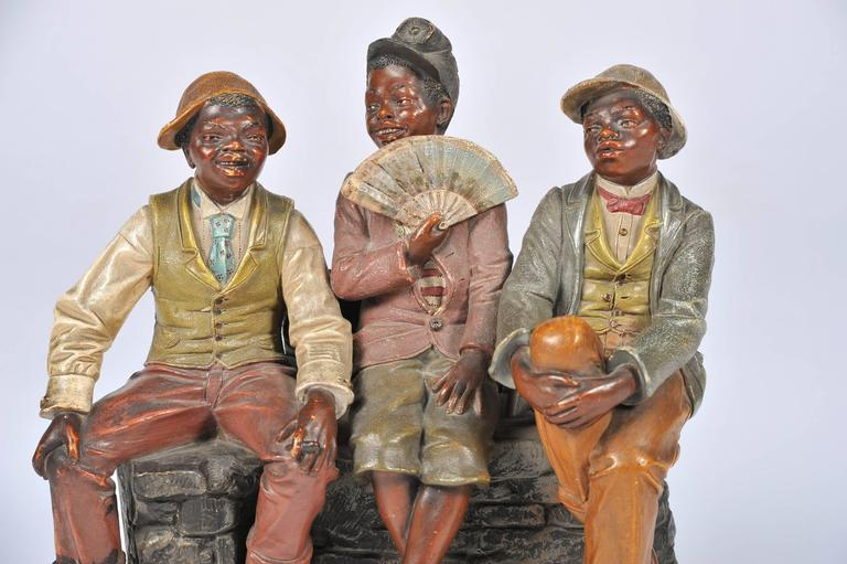 A very amusing late 19th century terracotta group, in the manner of 'Goldscheider' of three young black boys sitting on a wall.