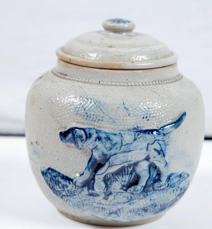 19th century blue glaze stoneware covered jar. Originally used as a humidor to store tobacco. Raised design in cobalt glaze depicting a hunting retriever dog.
