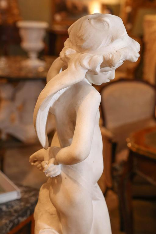 A lovely Carrara marble sculpture of a demure Cupid. Standing by a tree trunk with his quiver at his side.