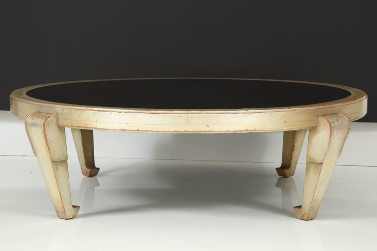 Large-scale James Mont silver leafed round coffee table with reverse painted glass insert. Wonderful patina to the silver.