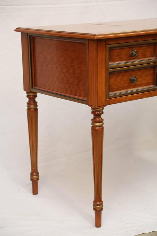 The rectangular top with hinged center panel lifting to a vanity mirror and storage compartment, over a frieze with drawers with gilt and bonded detailing flanking the kneehole; raised on turned tapering legs. Kneehole measures 25.5