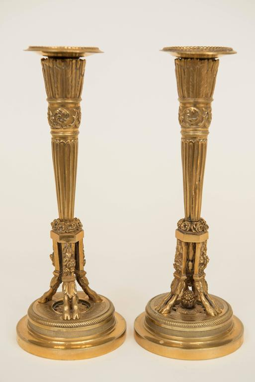 """Add some neoclassical """"bling"""" with these highly decorative hand chased gilt metal candlesticks! They have arrow feather detailing over floral, acorn and hoof foot decorations."""