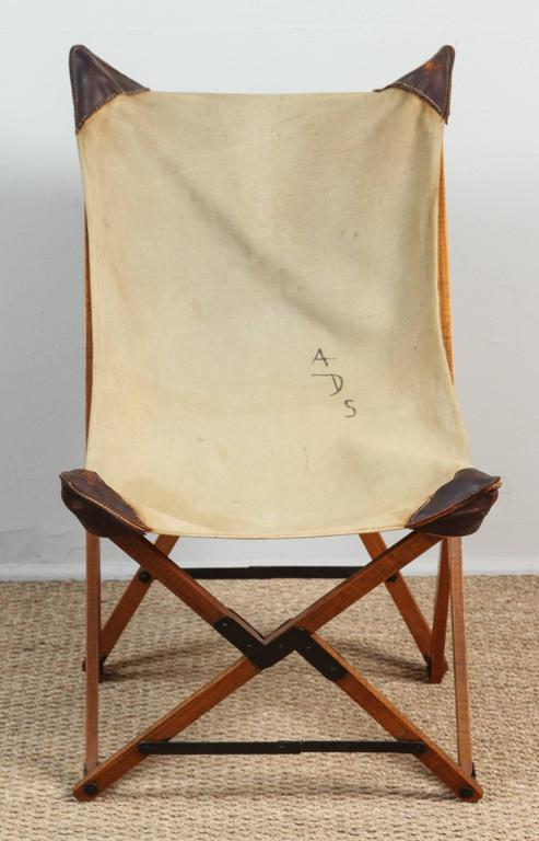 Pat McGann Gallery   Campaign chair with original heavy canvas seat. Initials ADS painted on to seat fabric. Leather corners have been hand re-sewn. Wooden base with metal hinges folds into a neat pile of sticks. Surprisingly sturdy.