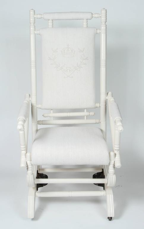 Antique spring rocking chair with new painted finish. Has been newly upholstered in Vintage linen, where seat back has been custom embroidered with crown and crest.