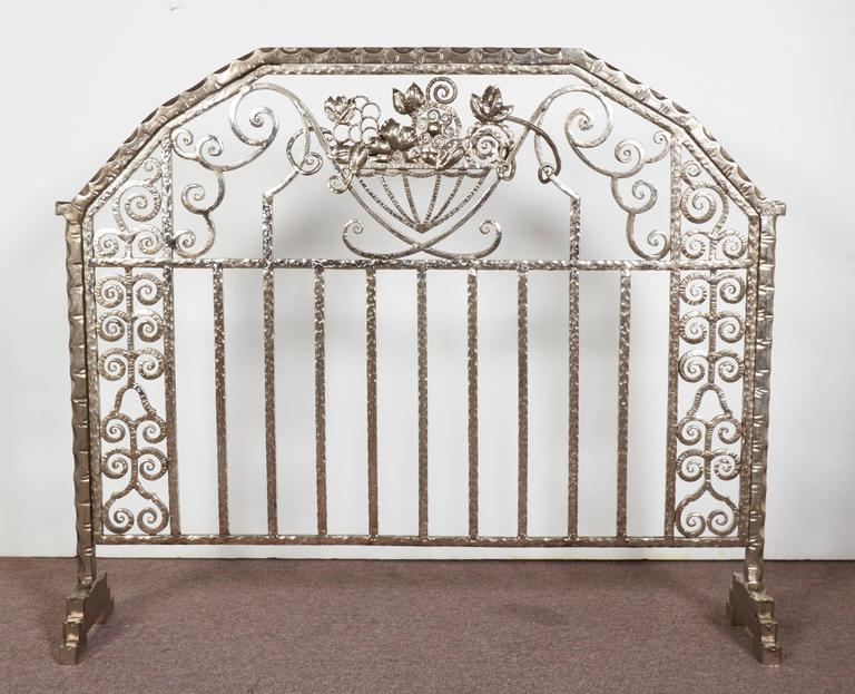 An exceptional pair of hand-forged iron Art Deco fire screens featuring overall linear and scroll detail with three dimensional central floral motif of superb martele hammering, unusually finished on both sides of the screen. signed: J. Vanloo