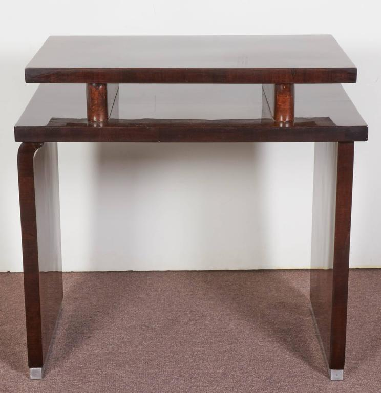 French Modernist stepped two tier cubist end table in bookmatched walnut. The top surface raised on bull nose plinths, while the bottom tier is supported by alternating curved and squared panels ending with metal strips. Specimen burl wood