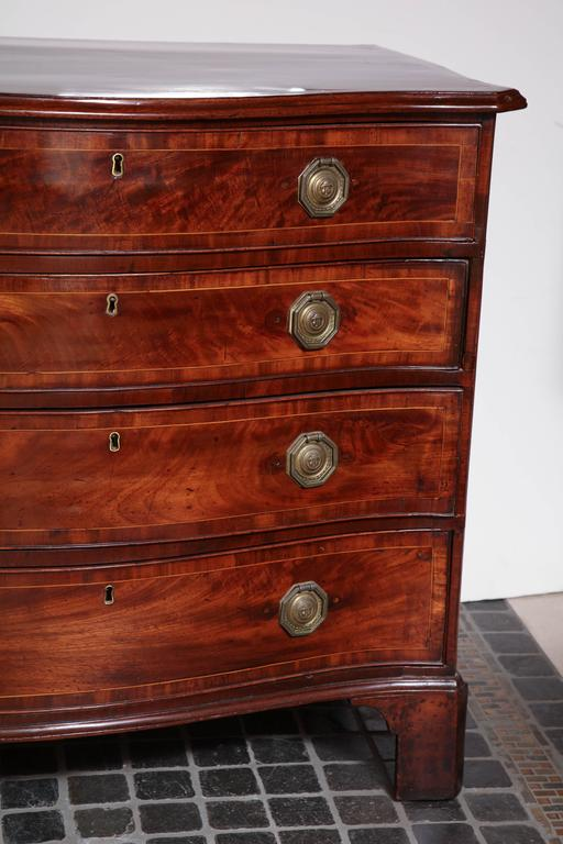 A fine English George III mahogany crossbanded serpentine chest of drawers with molded edge top, graduated drawers and bracket feet.