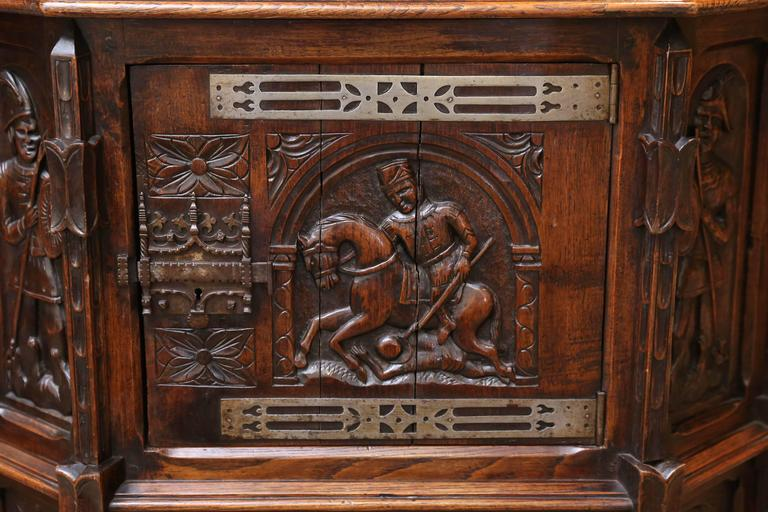 Handsome oak cabinet with a horseback rider carved in the centre front Carvings are on all sides of this interesting cabinet. The front opens with a sliding iron lock. It has one drawer in the centre.
