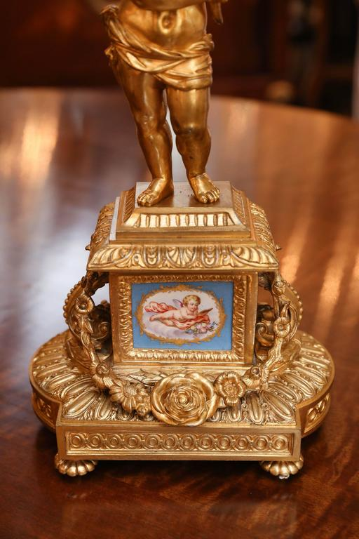 Beautiful pair of doré bronze candelabrum, 19th century. Putto holding The candelabrum each with six candleholders. Sevres style  porcelain mounts In Celeste blue.