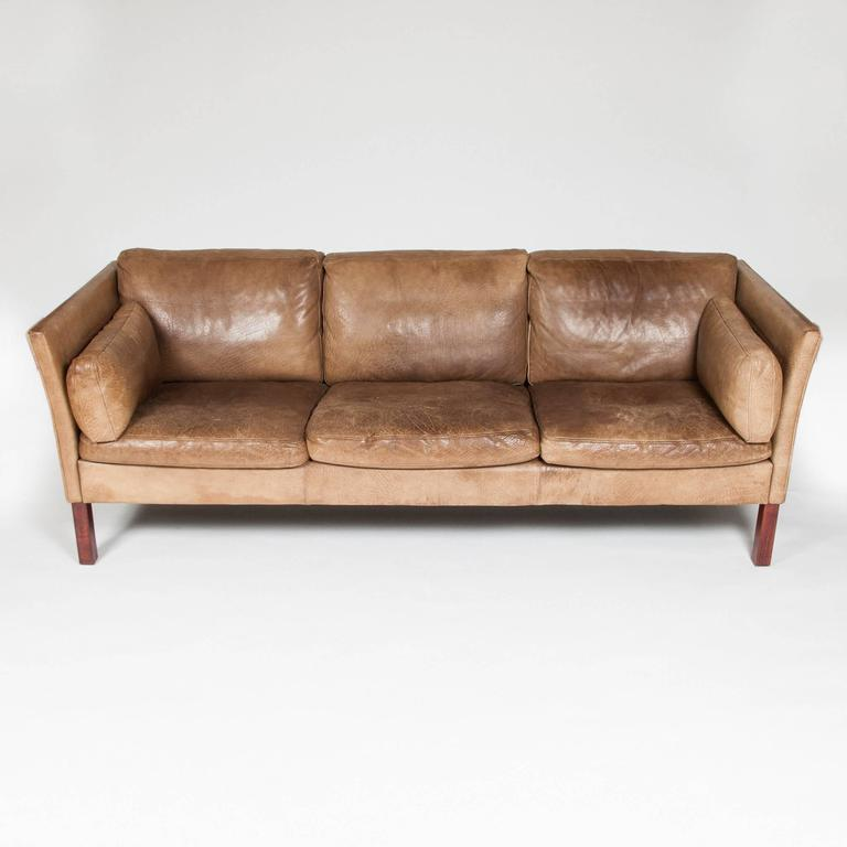 A Mid 1970s Three Seat Sofa Upholstered In Patinated Light Brown Buffalo  Hide, With