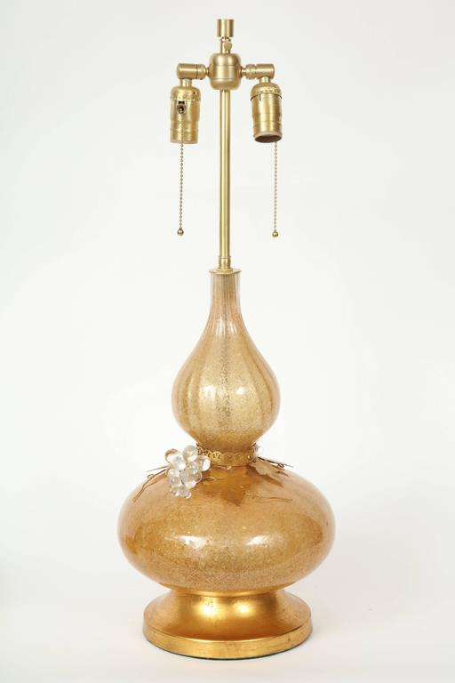 Mid-Century Murano glass genie bottle shaped lamps in a rich gold tone with crushed glass pieces applied to the interior. 22 karat gilt washed leaves and clear glass grapes adorn the cinched middle. Lamps rest on 22 karat gold washed brass bases.