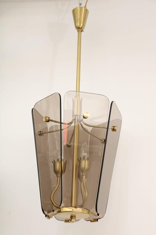 Mid-Century Italian satin brass framed pendant chandelier with six smoked glass panels. Pendant houses three-light sources and has been rewired for use in the USA. Lantern body measures 17.5 inches tall.