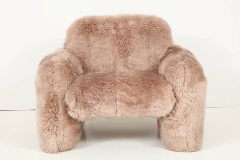 Dramatic and luxurious pair of club chairs upholstered in sandstone colored New Zealand sheepskin. The simplistic forms are the perfect platform to showcase the incredible soft and dense sheepskins. Chair frames are well constructed steel frames
