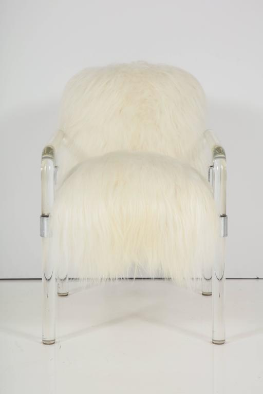 Pair of Pipeline series Lucite arm chairs designed by Jeff Messerschmidt in luxurious pure white long hair Arctic sheepskin. Upholstery is dense and extremely soft. Currently there is a pair available, $3400 each.