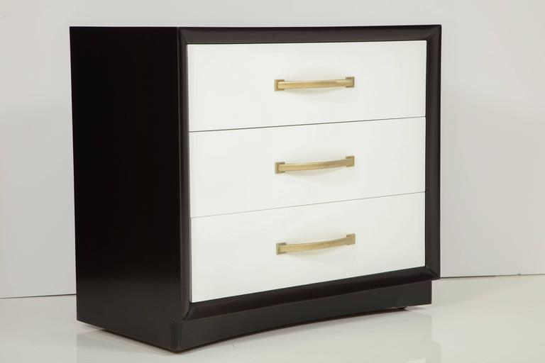 Mid-Century Classic pair of three-drawer chest of drawers featuring dark walnut stained cases and matte lacquer drawer fronts with brushed brass handles. Designed by T. H. Robsjohn-Gibbings for Widdicomb. Mint restored.