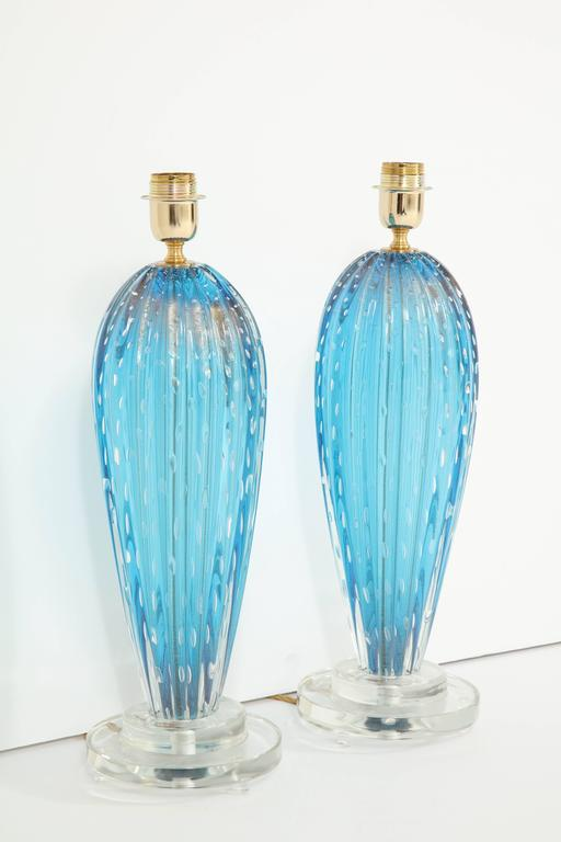 "A pair of Murano blown glass lamps in a stunning shade of blue. The lamps were created using the Pulegoso technique, resulting in the appearance of small ""bubbles."" The base is solid, clear Murano glass."