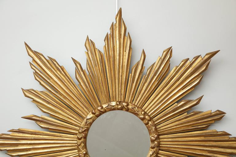 "We love sunburst ""soleil"" mirrors and this one is particularly striking. The center mirror is surrounded by a molded frame and sun rays in various lengths. Made in France, circa 1970."