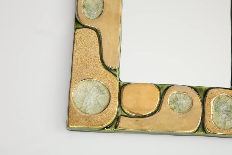 A small, but stunning mirror created by Francois Lembo, circa 1960, in France. The mirror is composed of pieces of stone within a gold crackle glazed ceramic frame. The border of the frame is painted in a green enamel and the back is felt.