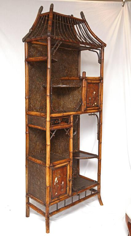 Superb 19th century English Japanese bamboo étagère recover with leather paper, carved doors and lacquer shelves. This is truly a Museum piece!