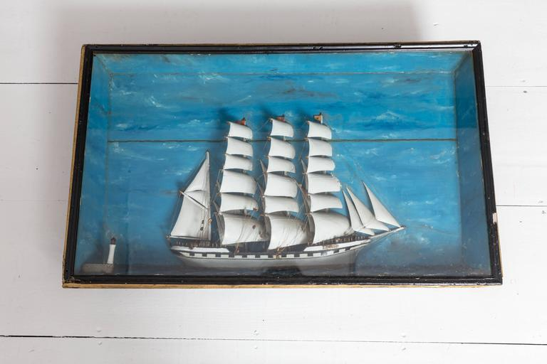French ship diorama with a large Schooner and small lighthouse. Hand-carved out of wood which includes the hull, sails, masts, and accoutrements. Mounted in a deep mitered wood frame with painted sea and sky background.
