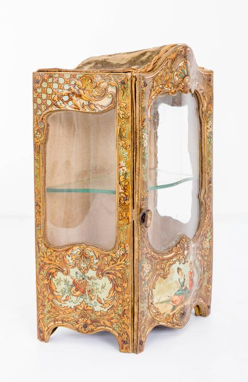 French miniature curio cabinet. Beautifully and realistically made papier mâché with curved glass on the sides and in the font. Door opens and has a glass shelf. Painting of figures and musical instruments on the sides and in the front. Would be a