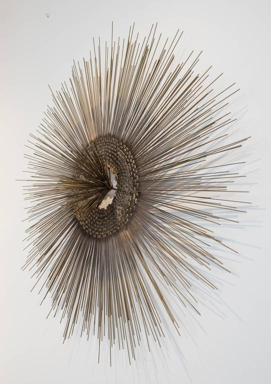 A splendid and Classic bronze-brass colored metal starburst wall sculpture with multiple metal rods surrounding a mesh interior with a metal rod