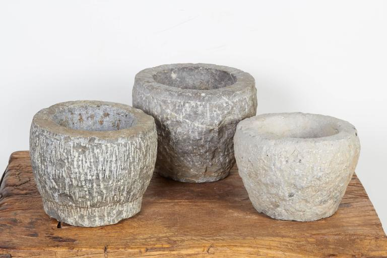 Three gracefully shaped, light colored solid stone mortars from Shanxi Province, China. These nicely textured pieces are suitable for many uses and work perfectly as shelf decoration. Priced individually. M819b.