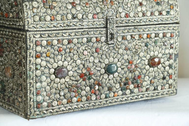 Large trunk covered in silver metal and assorted colored stones.