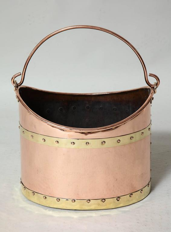 Fine English 19th century brass bound copper bucket having a bail handle, rolled lip, brass bands with studded copper riveted seams, the whole with well polished surface and of skilled craftsmanship.