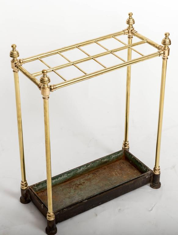 Twelve stick brass umbrella stand with iron basket and original drip tray.